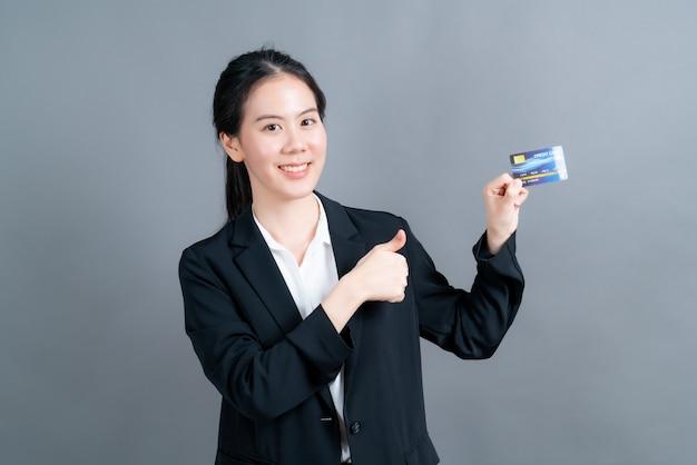 Retrato de uma adorável jovem asiática em panos de oficial, mostrando o cartão de crédito com espaço de cópia