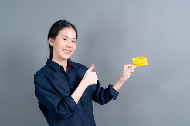 Retrato de uma adorável jovem asiática mostrando um cartão de crédito com espaço de cópia