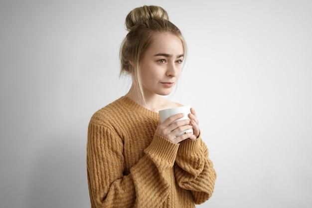 Retrato de uma adorável jovem encantadora com um penteado bagunçado segurando uma xícara grande, tomando um café fresco da manhã em casa