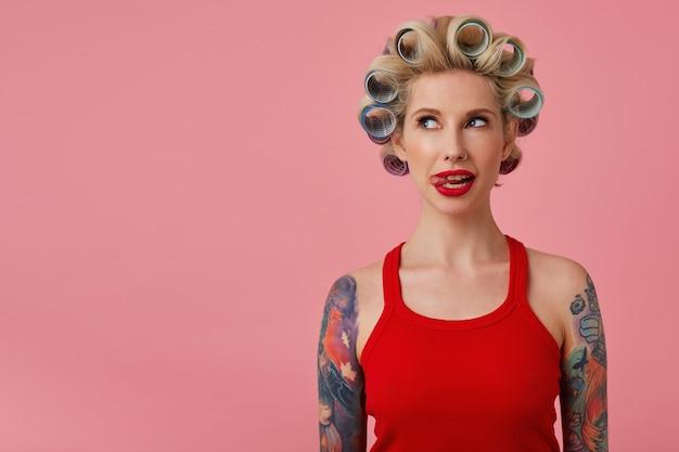 Retrato de uma adorável jovem loira com tatuagens e lábios vermelhos mostrando a língua enquanto olha para o lado, se preparando para o encontro e estando de bom humor, posando sobre fundo rosa em camisa vermelha