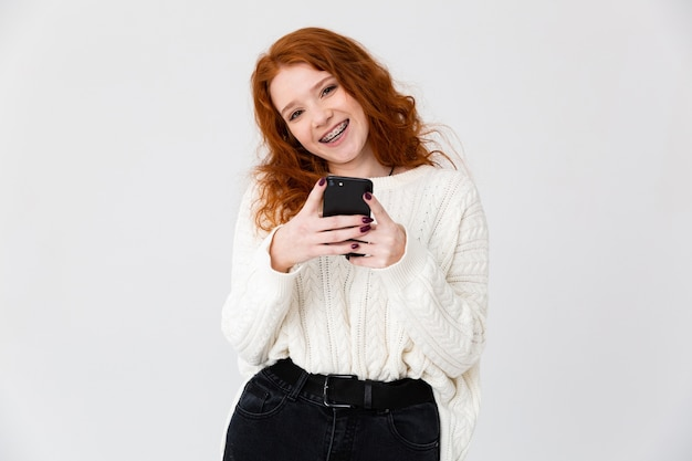 Retrato de uma adorável jovem ruiva de pé isolado sobre um fundo branco, usando telefone celular