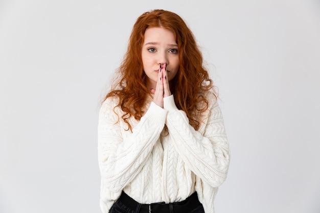 Retrato de uma adorável jovem ruiva em pé isolado sobre um fundo branco, orando