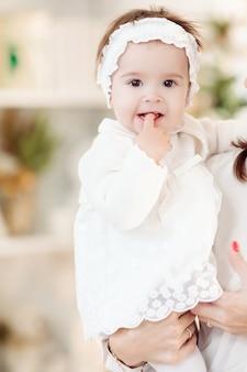 Retrato de uma adorável menina com bandana branca e vestido, mordendo o dedo enquanto está sentada nas mãos da mãe