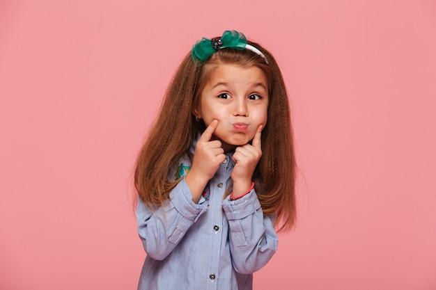 Retrato de uma adorável menina com cabelo ruivo longo bonito, explodindo suas bochechas, tocando o rosto