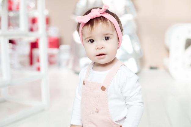 Retrato de uma adorável menina morena com tiara rosa com laço e um suéter branco olhando para frente