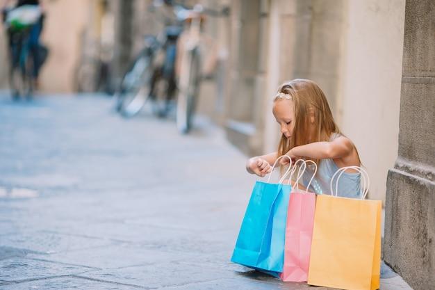 Retrato de uma adorável menina sentada com sacos de compras ao ar livre