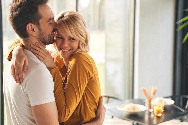Retrato de uma adorável mulher caucasiana, casada e animada, abraçando o marido amoroso na cozinha