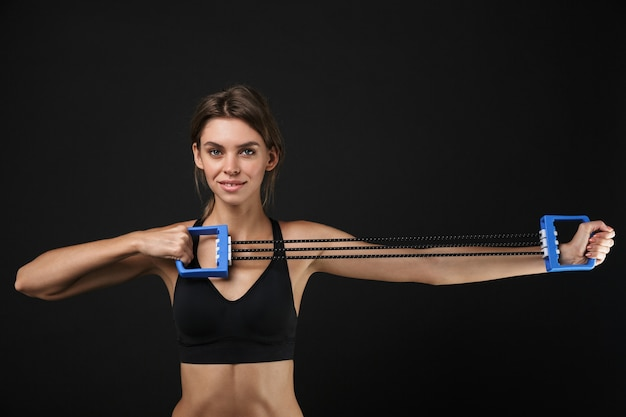 Retrato de uma adorável mulher caucasiana em roupas esportivas, esticando os braços com equipamento expansor durante treino no ginásio isolado sobre fundo preto