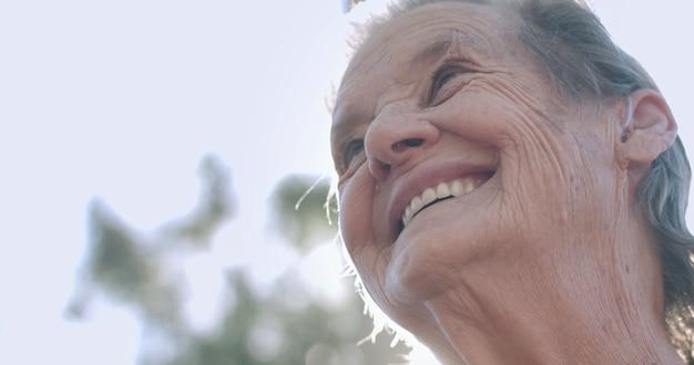 Retrato de uma adorável mulher idosa no parque de verão, olhando para o horizonte e sorrindo.