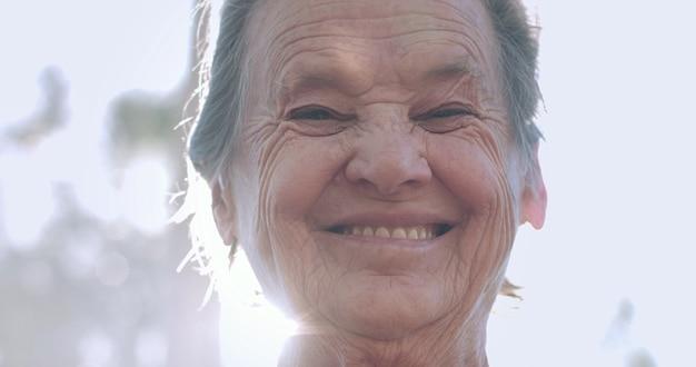 Retrato de uma adorável mulher idosa no parque de verão sorrindo.