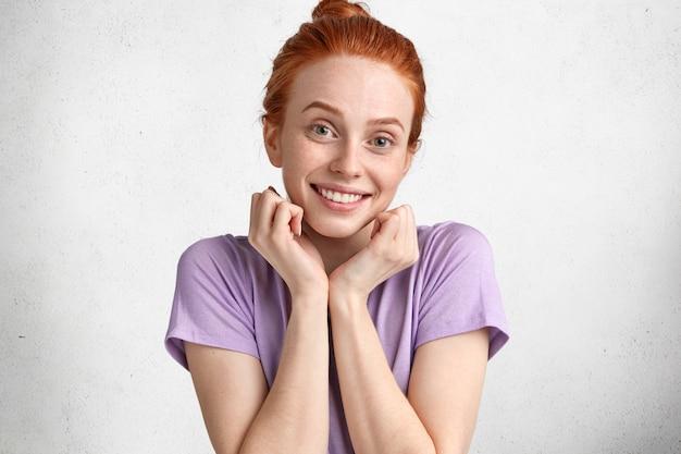 Retrato de uma adorável mulher ruiva encantada com a pele sardenta sorrindo feliz para a câmera, satisfeita com as novas compras, vestida casualmente