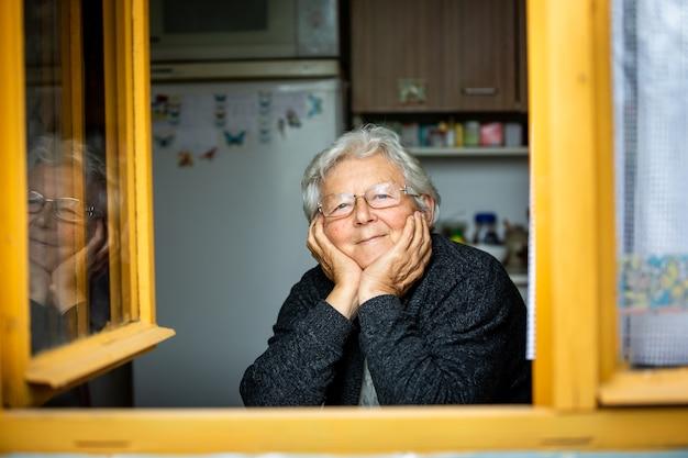 Retrato de uma adorável mulher sênior ou avó olhando pela janela e sorrindo, aposentada