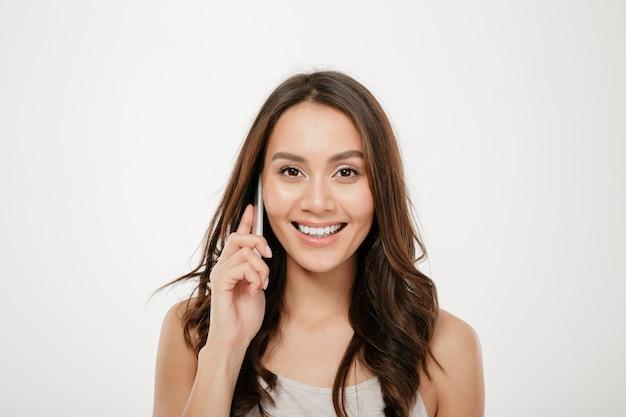 Retrato de uma adorável mulher sorridente com longos cabelos castanhos falando no celular, tendo uma conversa agradável sobre branco