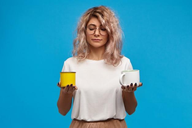 Retrato de uma adorável secretária jovem, elegante, com óculos redondos e duas xícaras nas mãos