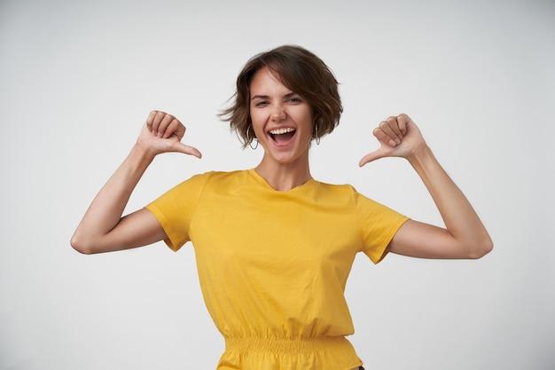 Retrato de uma adorável senhora autoconfiante com penteado casual, olhando alegremente e apontando alegremente para si mesma, em pé com as mãos levantadas