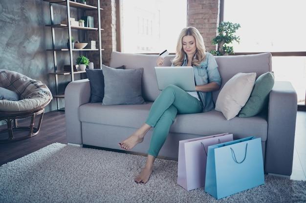 Retrato de uma adorável senhora de cabelos ondulados segurando laptop sentar sofá