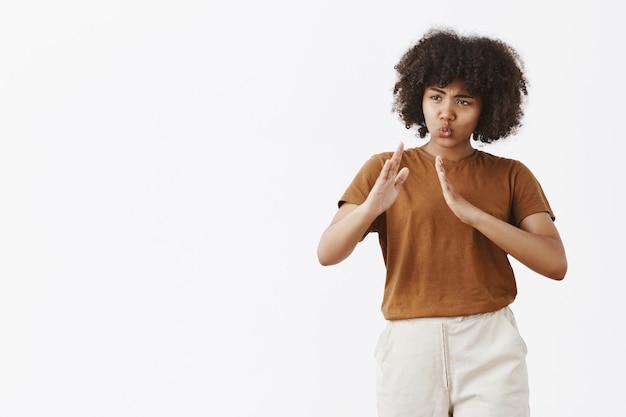 Retrato de uma afro-americana divertida e fofa brincalhona de cabelos cacheados em uma camiseta da moda levantando as palmas das mãos em pose de kung fu dobrando os lábios sobre a parede cinza