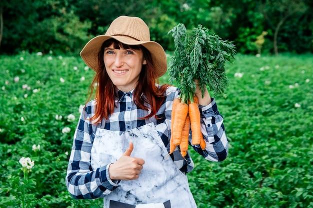 Retrato de uma agricultora segurando um cacho de cenouras em um chapéu de palha no fundo de uma horta