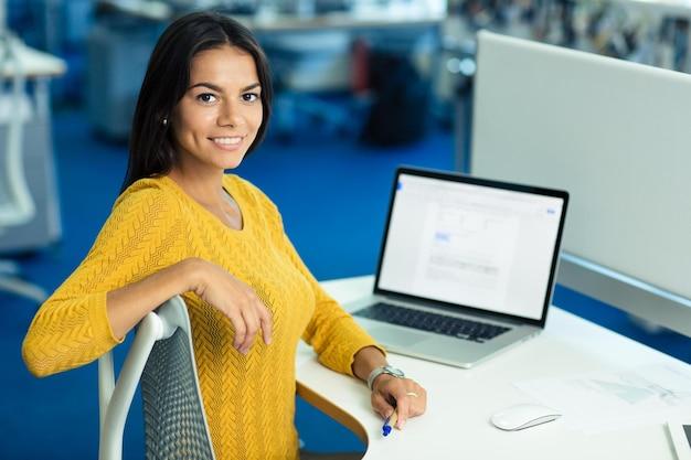 Retrato de uma alegre empresária casual sentada à mesa com o laptop no escritório