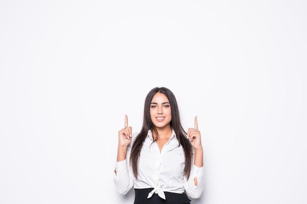 Retrato de uma alegre empresária vestida de terno apontando o dedo para longe no espaço da cópia isolado no branco