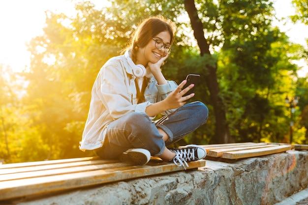 Retrato de uma alegre feliz fofo jovem estudante garota usando óculos, sentado ao ar livre no parque natural, usando telefone celular.