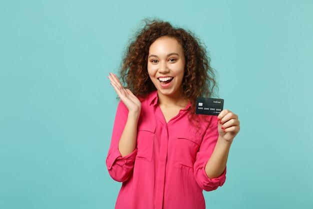 Retrato de uma alegre garota africana em roupas rosa casuais, segurando o cartão do banco de crédito isolado no fundo da parede azul turquesa no estúdio. emoções sinceras de pessoas, conceito de estilo de vida. simule o espaço da cópia.