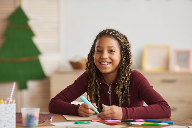 Retrato de uma alegre garota afro-americana olhando para a câmera enquanto desfruta de desenho sentado à mesa no interior da casa, copie o espaço