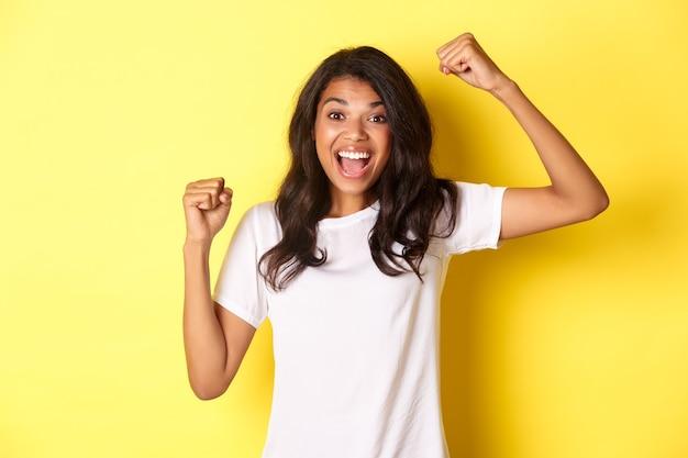 Retrato de uma alegre garota afro-americana vencendo e comemorando a vitória, levantando as mãos