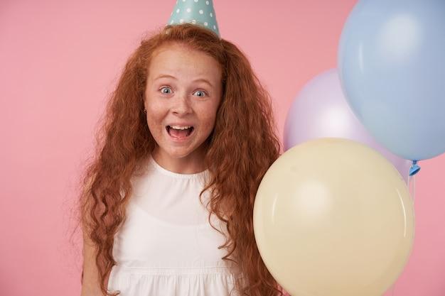 Retrato de uma alegre garota ruiva com cabelo longo cacheado, vestido branco e boné de aniversário, ficando animada e surpresa ao ganhar um presente de aniversário, olhando para a câmera sobre fundo rosa