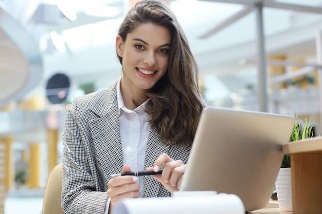 Retrato de uma alegre jovem empresária sentado à mesa no escritório e olhando para a câmera.