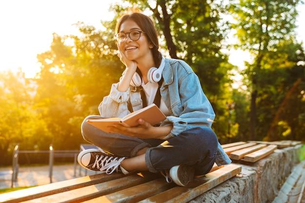 Retrato de uma alegre jovem estudante de óculos, sentada ao ar livre no parque natural, ouvindo música com fones de ouvido e lendo um livro