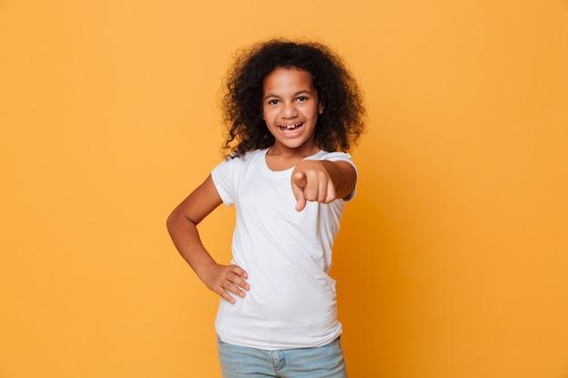 Retrato de uma alegre menina africana apontando o dedo