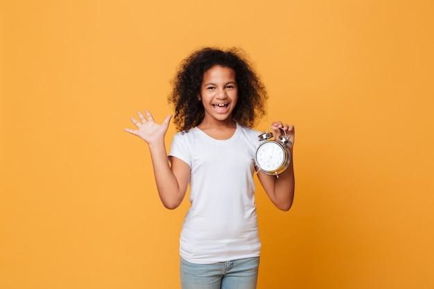 Retrato de uma alegre menina africana segurando o relógio despertador