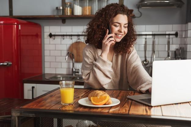Retrato de uma alegre mulher caucasiana usando laptop e celular na mesa do interior da cozinha, enquanto toma o café da manhã em casa