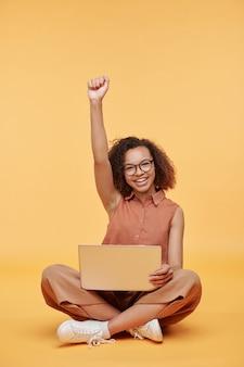 Retrato de uma aluna animada sentada com o laptop sobre os joelhos e levantando o braço contra um fundo amarelo