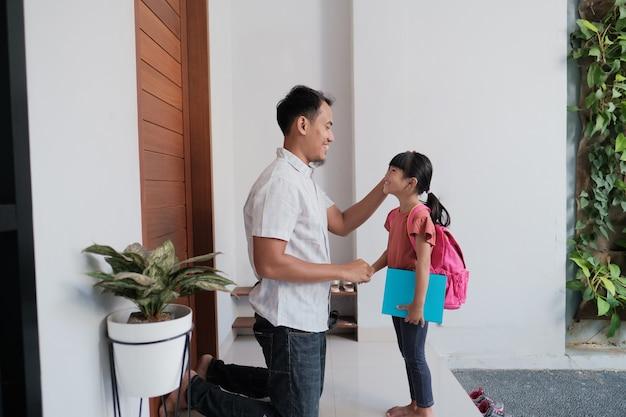 Retrato de uma aluna da escola primária indonésia apertando e beijando a mão do pai antes de ir para a escola