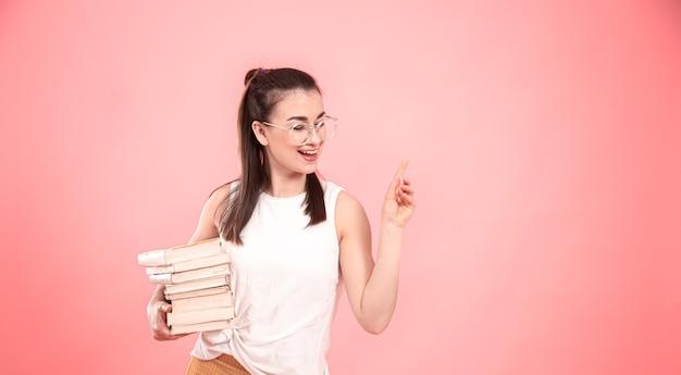 Retrato de uma aluna de óculos com livros nas mãos. conceito de educação e hobbies.