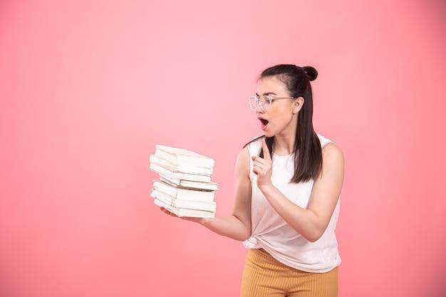 Retrato de uma aluna de óculos posando com livros nas mãos dela. conceito de educação e hobbies.