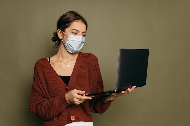 Retrato de uma aluna em uma máscara protetora com um laptop sobre um fundo verde