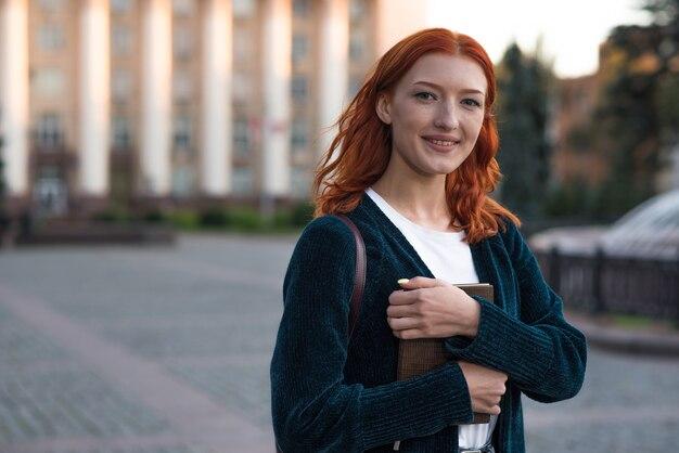Retrato de uma aluna linda, jovem e atraente ruiva caucasiana com uma mochila.