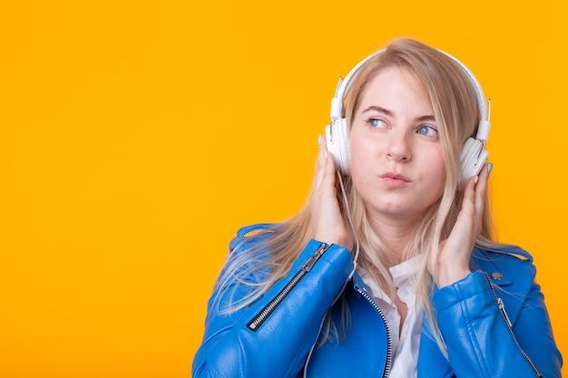 Retrato de uma aluna loira muito jovem segurando um smartphone com uma jaqueta de couro azul