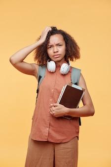 Retrato de uma aluna negra carrancuda e intrigada em roupa casual em pé com livros e coçando a cabeça em confusão