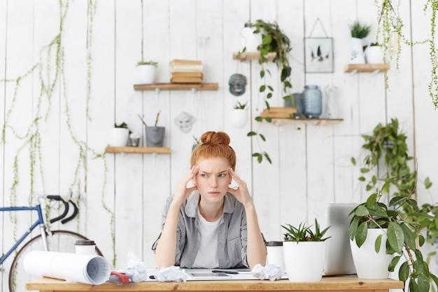 Retrato de uma arquiteta caucasiana sentada em seu local de trabalho sobre esboços