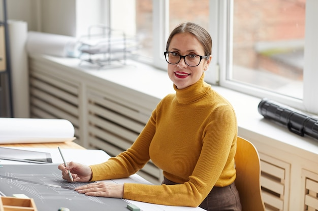 Retrato de uma arquiteta sorridente, desenhando plantas e planos enquanto trabalhava na mesa do escritório e,