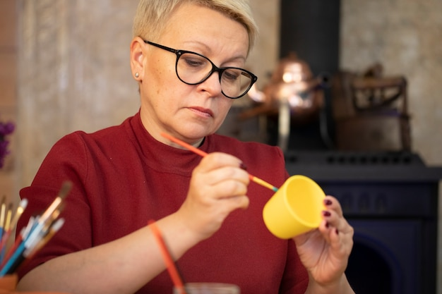 Retrato de uma artista feminina pintando em uma panela de barro amarelo em um estúdio caseiro de arte