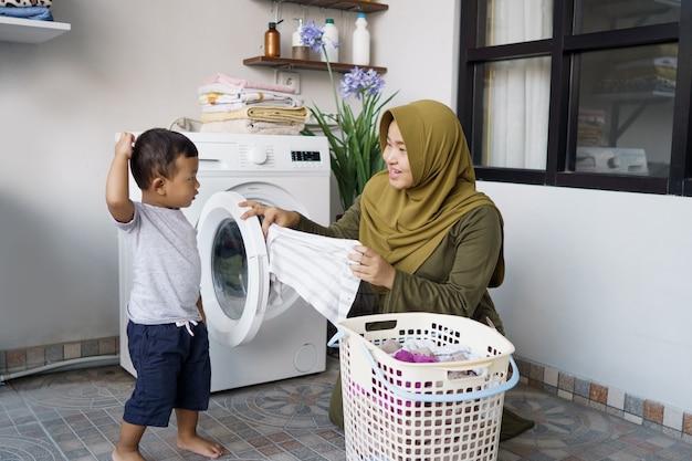 Retrato de uma asiática feliz mãe e filho lavando roupa juntos em casa