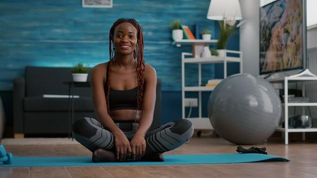 Retrato de uma atleta negra sentada em posição de lótus no chão, aproveitando o treino matinal