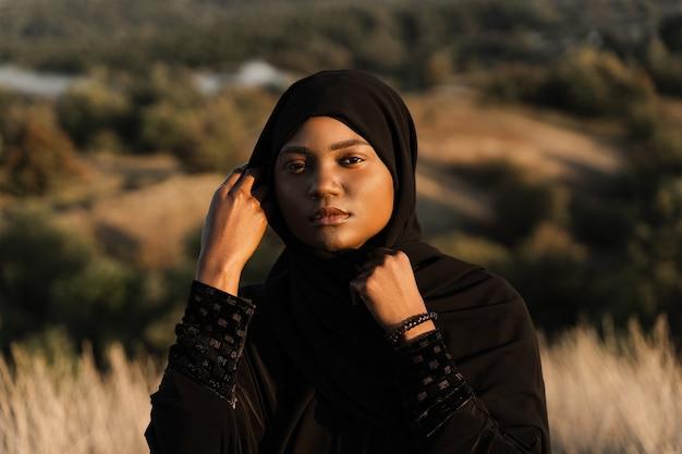 Retrato de uma atraente garota africana no manto tradicional preto. salah orando em deus.