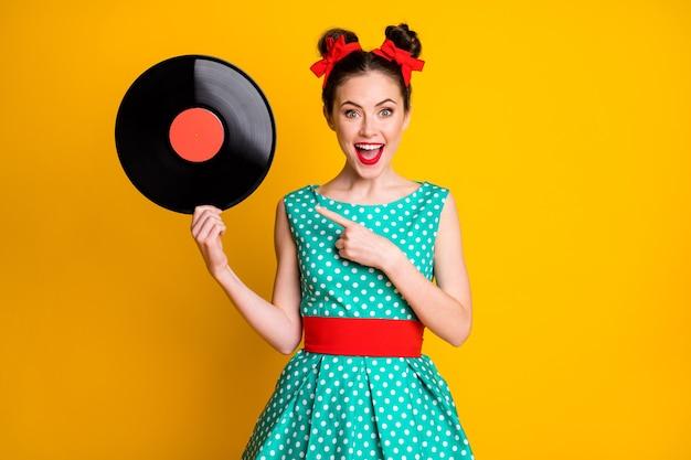 Retrato de uma atraente garota alegre e surpresa segurando nas mãos, mostrando um disco de vinil isolado em um fundo de cor amarela vibrante