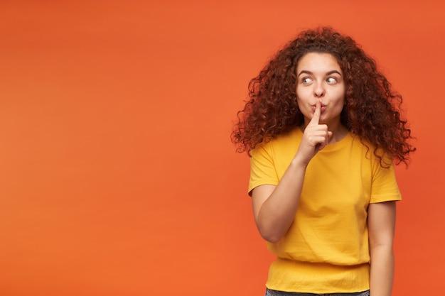 Retrato de uma atraente garota ruiva com cabelo encaracolado, vestindo uma camiseta amarela